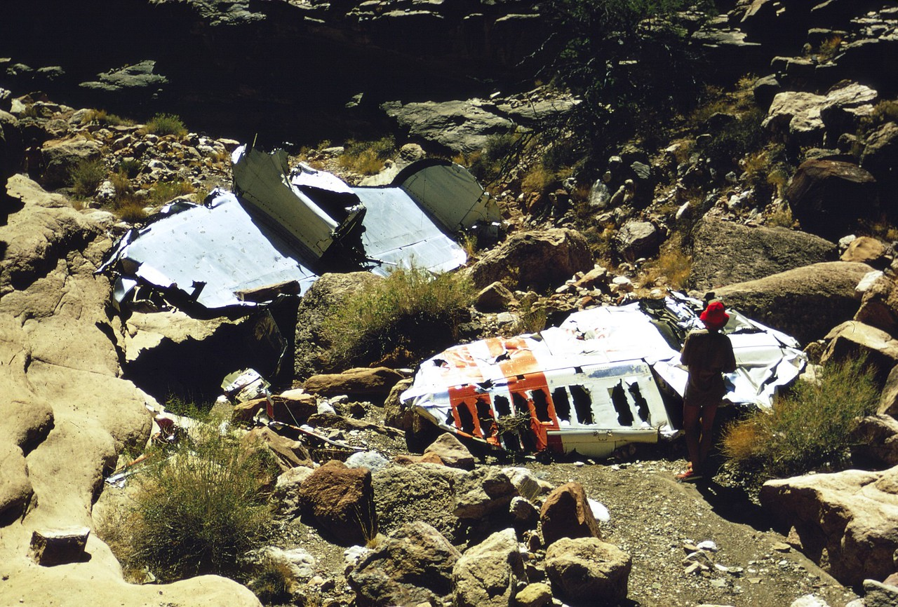 "TWA TAIL SECTION IMPACT SITE - 1972<br /> <br /> Over time, park rangers would push the Constellation's tail and vertical fins further into ""crash canyon"" as seen in this photo from 1972. The purpose was to conceal the wreckage from rafters and hikers at river level. This however did not stop curious river runners. (LostFlights Archive Photo)"