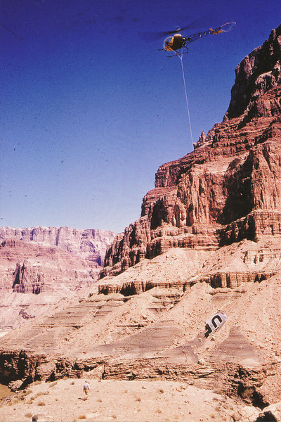 A Bell 47 helicopter lifting the DC-7's port wingtip from Temple Butte. This fragment would later be used to determine the angle that the two airliners collided. (LostFlights Archive Photo)