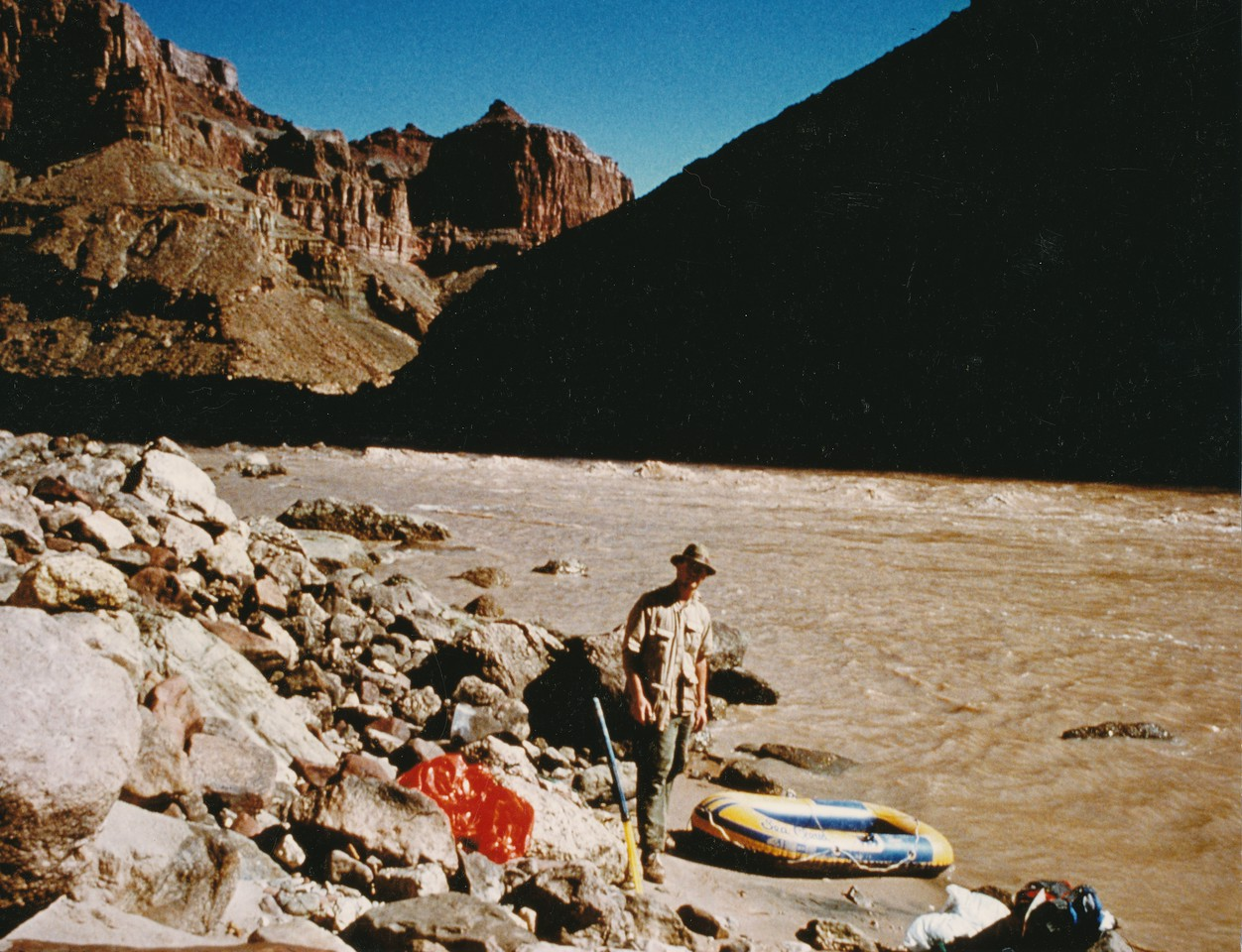 On the West/Chuar Butte side of the river after a successful crossing during my October 1990 trip. <br /> <br /> Crossing the Colorado River is without question the most dangerous part of the journey. The water temperture maintains a constant of 45-49 degrees year round. The currents are very strong and deadly whirlpools are common. In the four hike/raft trips I have made, operating on the river has been very challenging.