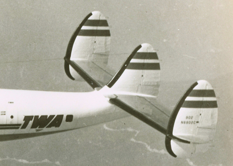 TAIL SEPARATION / PASSENGER CABIN DECOMPRESSION:<br /> <br /> During the CAB investigation, it was discovered that a  majority of the collision damage to TWA Flight 2 occurred in this area of the aircraft.<br /> <br /> The UAL DC-7's left wing tore across the right and center tail fins. The left wing continued to disintegrate as it tore down and through the pressurized cabin from the lounge (square window) and stopping just prior to the main passenger entrance door (small round window). <br /> <br /> With the tail mounts weakened, the entire tail structure separated, pulling with it the upper cabin structure and interior items.