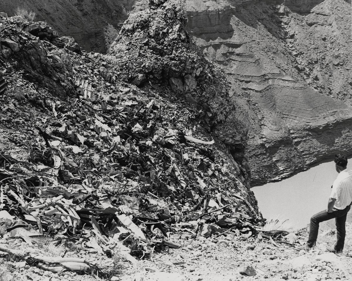 This photo taken on Chuar Butte illustrates the danger of this particular crash site location. <br /> <br /> The wreckage debris lies on a slope that gradually steepens to a vertical drop of several hundred feet. Needless to say, United Air Lines having 20 years prior risked lives to recover crash victims, did not want to continue to risk lives on a clean-up operation. (LostFlights Archive Photo)