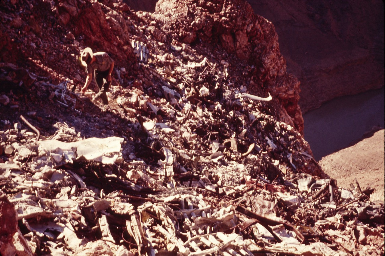 UAL DC-7 IMPACT SITE - 1975<br /> <br /> A park ranger in 1975 looks over the wreckage of the UAL DC-7 at the main impact site on Chuar Butte. (1975 NPS Photo)