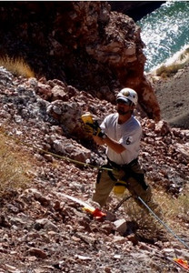 Grand Canyon Park Service Archaeologist Ian Hough documents the impact site of UAL Flight 718. He is tethered by a static line to prevent him from falling down the 350' cliff directly behind him. (NPS Photo)