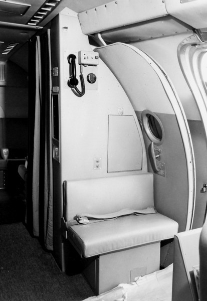 """This passenger cabin photograph illustrates an intact cabin interior bulkhead on a TWA Super Constellation. <br /> <br /> The small seat, also known as a """"Jump-Seat"""" can be seen located in front of the bulkhead and next to the main entrance door. This seat is used by the Hostess."""