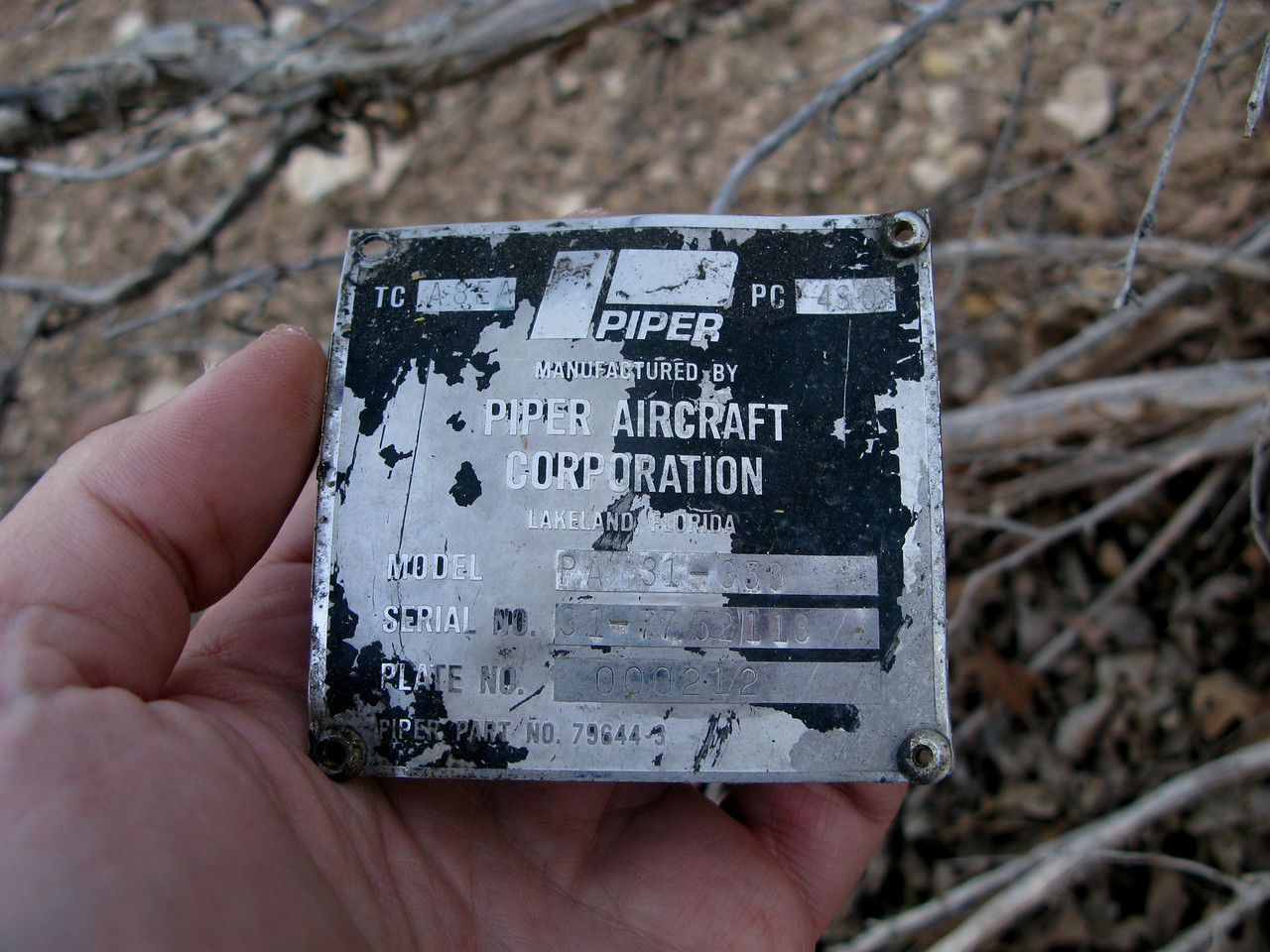 "The aircraft manufacture's data placard is basically the plane's ""Birth Certificate"". It contains the aircraft model type and serial number. <br /> <br /> This metal placard is riveted to the outside structure just below the main cabin door. It was found next to some brush at the site."