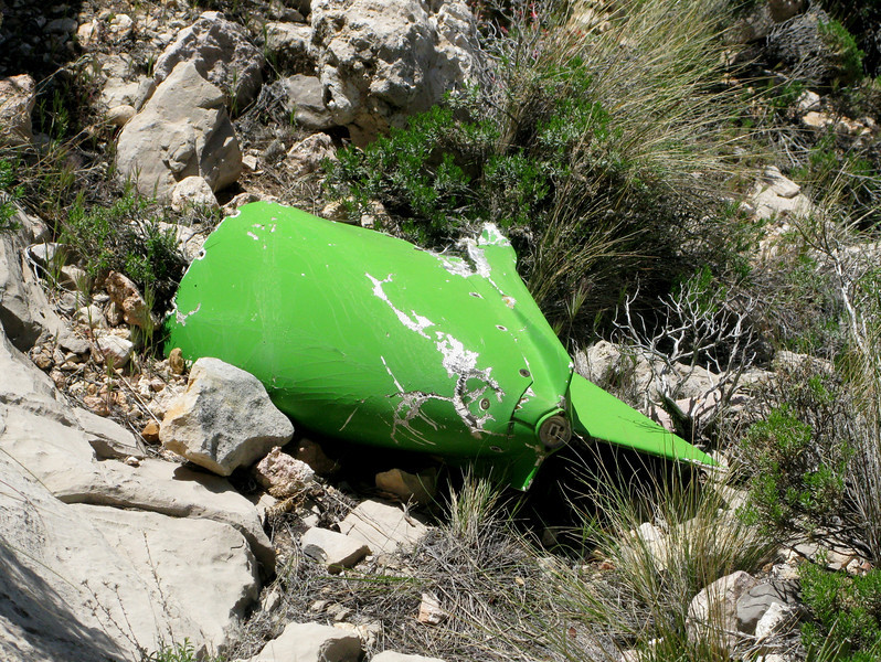 Even the aircraft's fiberglass tailcone failed to escape damage and was thrown down the ledge and nearly off the cliff.