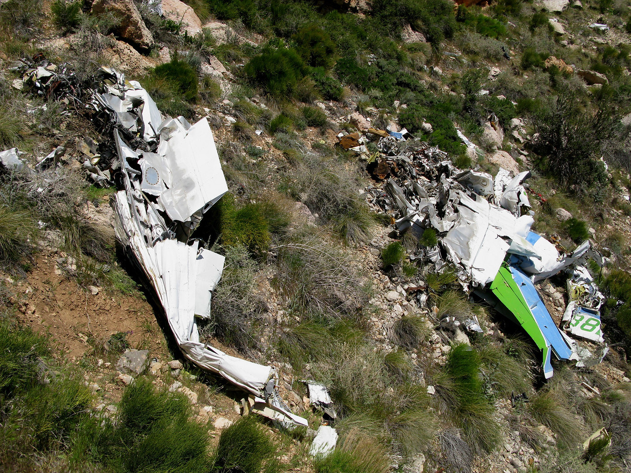 The main wreckage of Flight 88 is situated on a talus slope angled at about 45-50 degrees. The tail section, fuselage, and right wing are on the right side of the photo while the remains of the left wing are on the left side of the photo.