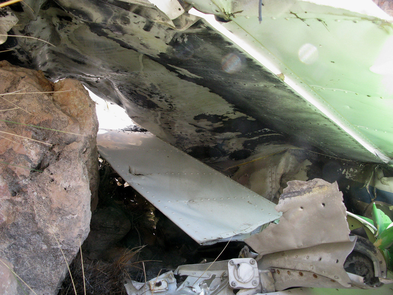 The top of the inverted right wing shows signs of the post crash fire damage to it's surface.