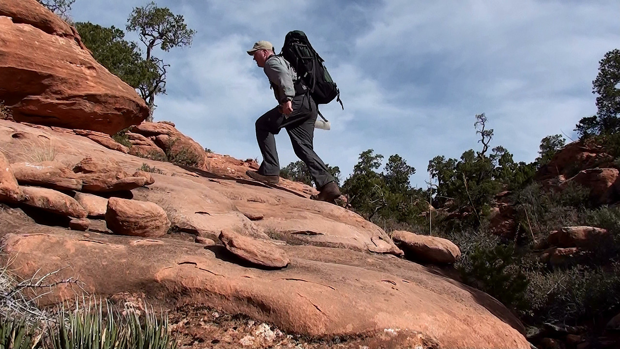 In some places the sandstone benches were easy climbs while in other places it required me to lower my heavy backpack by rope down steep terrain. <br /> <br /> There would be no water pockets or springs along this route leaving me to pack in about 4 gallons of water.