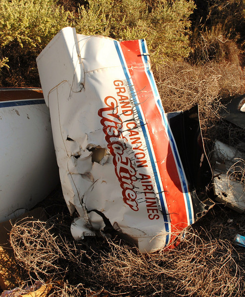 A destroyed engine nacelle painted with the airline titles and aircraft name sits amid other debris.