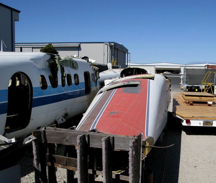 """A NEW HOME FOR """"CANYON 5"""".<br /> <br /> In storage amid other wrecked Twin Otters, """"Canyon 5"""" was essentially """"buried"""" where it was """"born"""". During 1987, the Twin Otter known as """"Canyon 5"""" was modified to a VistaLiner by R.W. Martin, Inc. here at their facility in Southern California.<br /> <br /> The plane will eventually be salvaged for parts to be used on other deHavilland Twin Otter aircraft.<br /> <br /> (THE END)"""