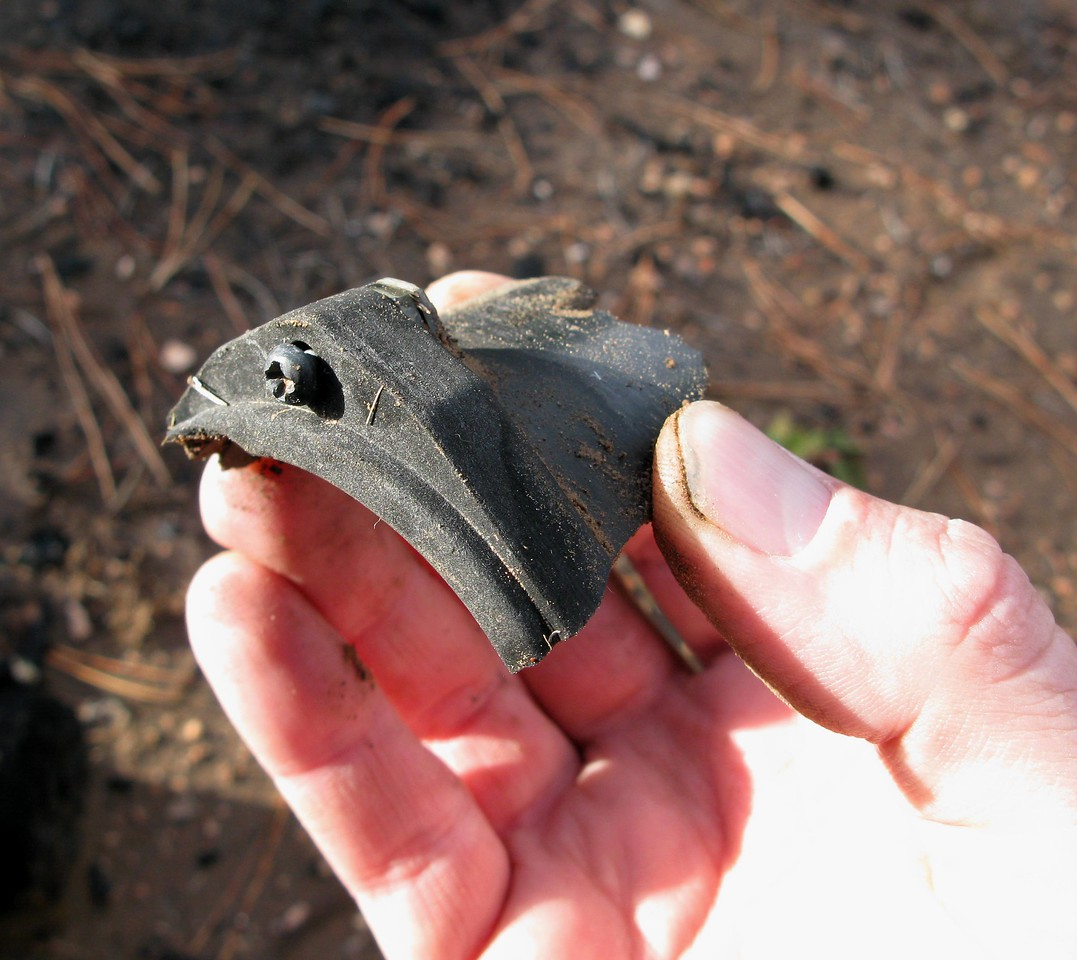 The corner fragment of a shattered aircraft flight instrument case was located near the fuselage main impact site.