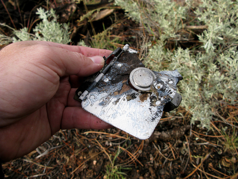 This burned and melted small access door with an attached latch mechanism may have come from the engine cowling area.<br /> <br /> There was no post crash fire from this accident, so this burn damage occurred during the prescribed management fire years later.
