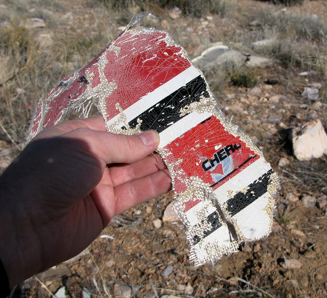 """With a combination of impact and decades of weathering erasing all but four and a half letters, the name """"CHEROKEE"""" can be deciphered from this fragment.<br /> <br /> The aircraft's overall white with red and black scheme was standard Piper manufacturer colors and scheme."""