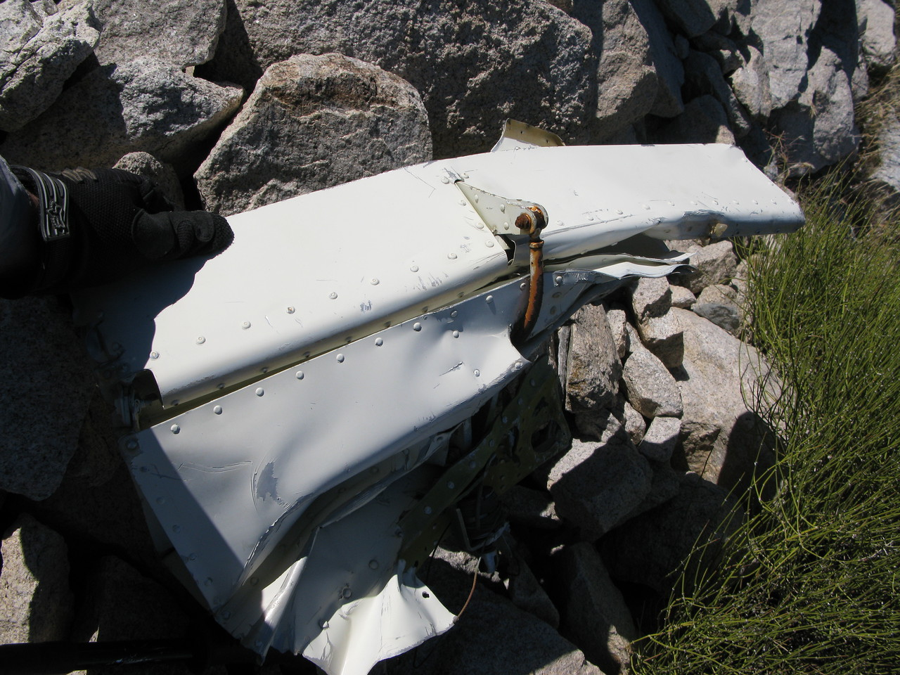 The aileron trim tab was barely recognizable. In a catastrophic accident such as this, the aileron trim tab can be confused with the elevator trim/anti-servo tab. The big difference is the larger attach point on the aileron's tab.