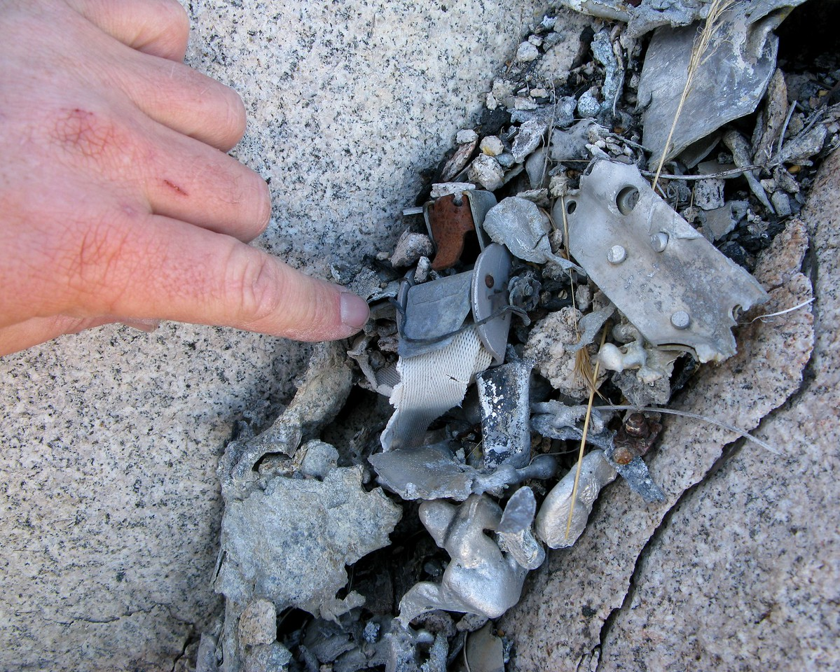 Amid the molten aluminum, I located this small cargo strap buckle. <br /> <br /> With a few years of flying these particular aircraft, I recognized these small straps. They were commonly used to secure items in the two nacelle wing lockers.