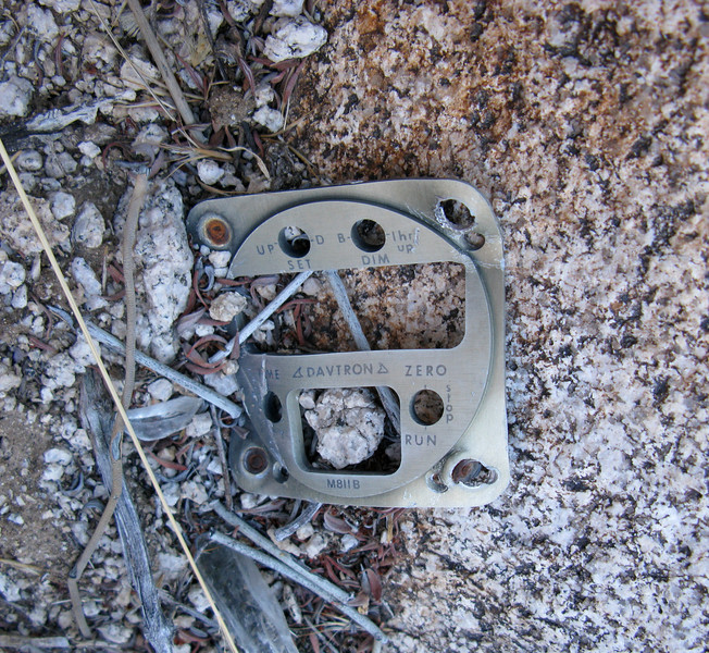 The remains of the aircraft's digital clock was located near some boulders. In this case, only the front cover plate was found from this Davtron M811B.