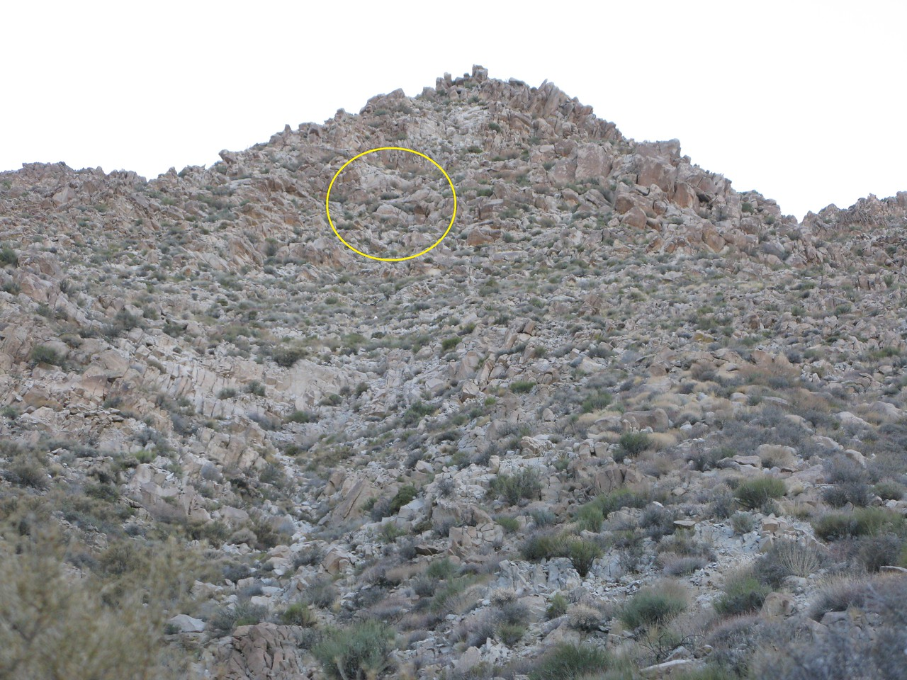 Small fragments of wreckage littered the site with many fragments concealed around and under boulders and rocks.<br /> <br /> The yellow circle illustrates the approximate location of the LVA50's point of impact (POI) several hundred feet above from where the first piece of wreckage was found.<br /> <br /> From this point on, the slope of the mountain begins to steepen to around 60-70 degrees. The terrain is so unstable that literally every rock I step on either slides or falls from under my feet.