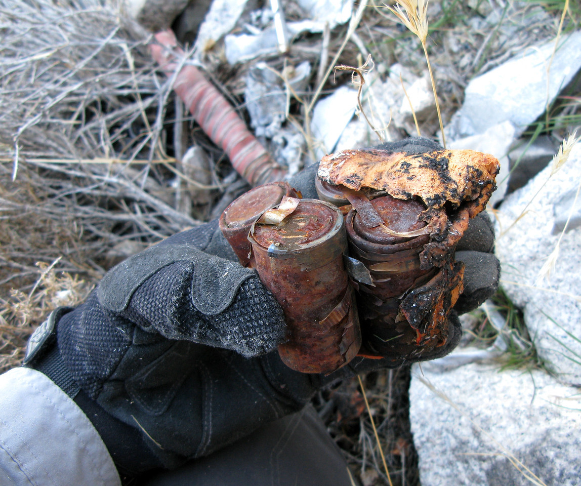 This cluster of burned D-Cell batteries located near the main impact point once powered the aircraft's Emergency Locator Transmitter (ELT). <br /> <br /> The ELT had activated at the moment of impact and the transmitted signal helped search and rescue narrow the aircraft's ultimate location. The signal eventually stopped transmitting early in the search effort.<br /> <br /> This evidence illustrates the ELT was ultimately consumed in the post-crash fire.