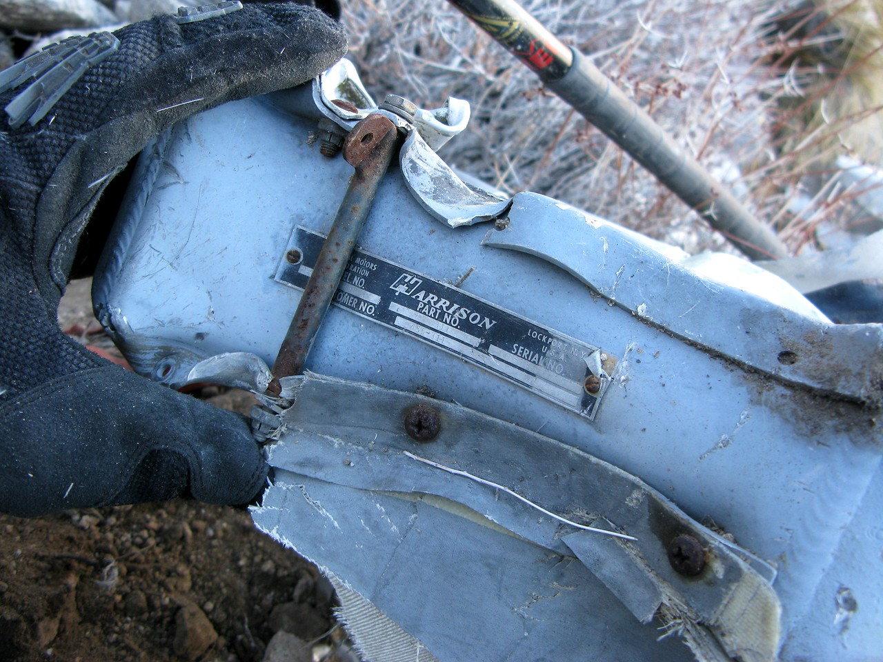 A data tag on the oil cooler identifies the manufacturer as Harrison Industries.