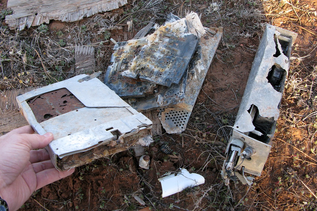 This collection of burned aircraft radios give silent testimony to the severe post impact fire. Had the fire spread, there is no doubt the wreckage would have been located sooner.