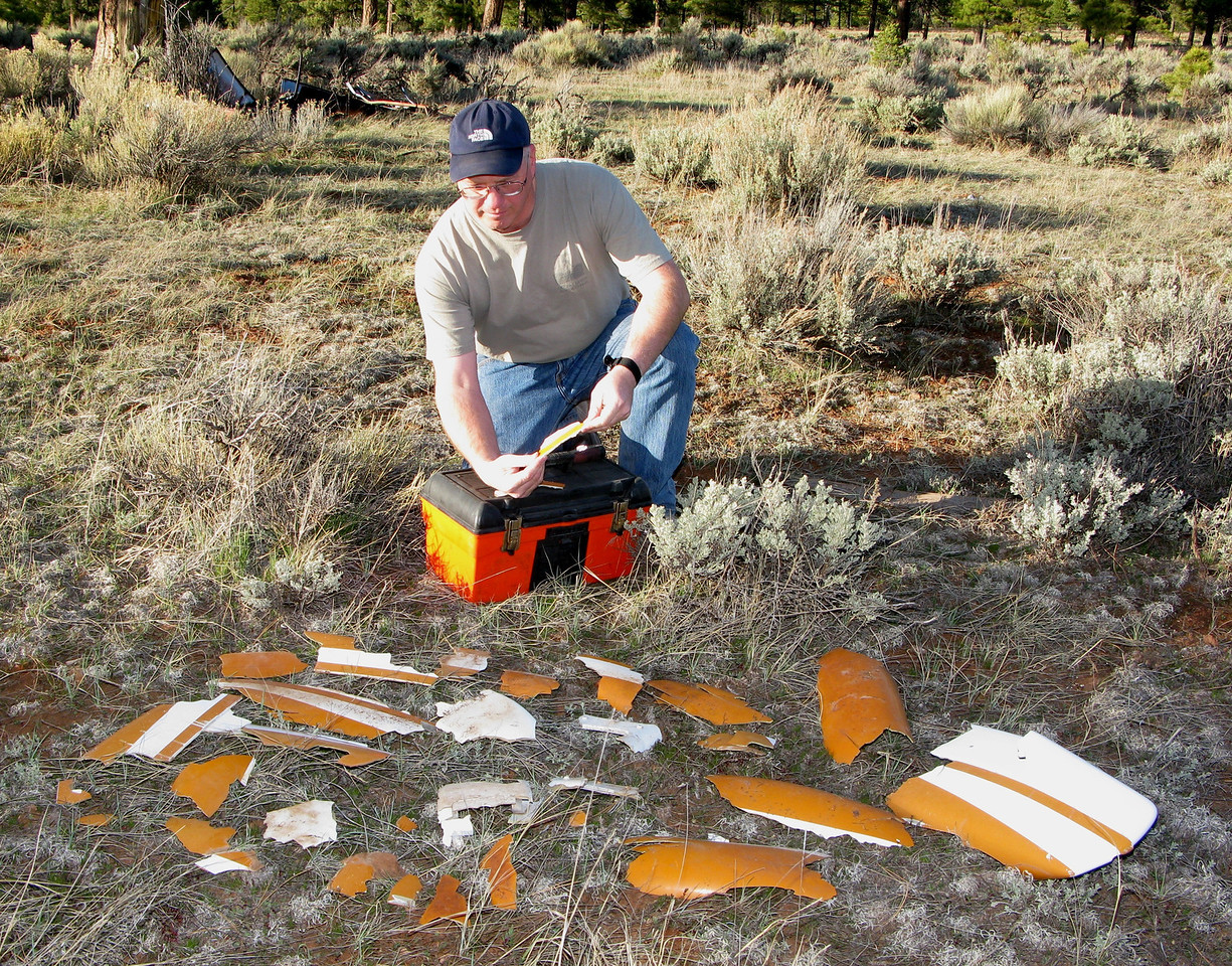 "PUTTING THE ""PUZZLE"" TOGETHER<br /> <br /> The paint color and plastic thickness matched perfectly with the fragments I found at the crash site, so I made an effort to see if I could find a fragment that would match.<br /> <br /> I gathered all the wheel fairing fragments that I could find in the debris pile and laid them out. I started one by one putting the corners together as if it were a puzzle."