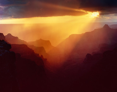 Grand Canyon National, AZ/Park North Rim, Cape Royal. Sunset rays light up passing rain strorm and the ridges below Cape Royal. 1090h aed