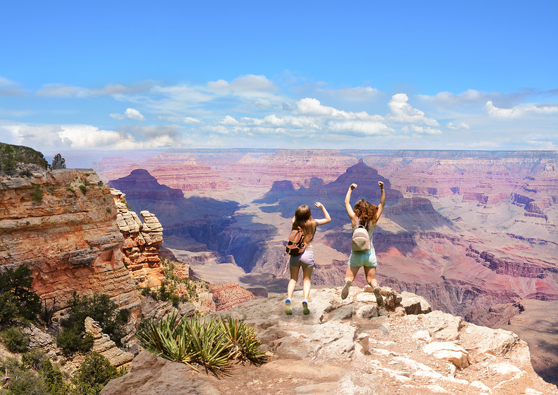 People with hands up jumping  and having fun on the top of the mountain. Girls on vacation in  beautiful  mountains looking at coastal landscape..Grand Canyon National Park, Arizona, USA