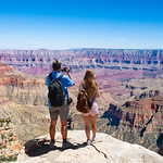Couple on hiking trip. Man using his camera. Beautiful mountain landscape in Arizona. North Rim, Grand Canyon National Park, Arizona, USA