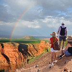 Family  hiking on vacation,relaxing on top of the mountain, looking at beautiful rainbow at sunset , mountains landscape. Grand Canyon National Park, Arizona, USA.