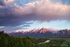 The Grand Teton mountains being lit by the rising sun as the Snake River winds through the valley.