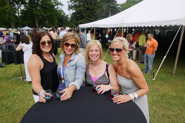 Record-Eagle/Keith King<br /> Lisa Krauss, from left, of Midland, Julie Carnes, of Merrill, Jessica VanBevern, of Auburn and Cheri Quandt, of Saginaw, during the Traverse City Wine and Art Festival at the Village at Grand Traverse Commons.