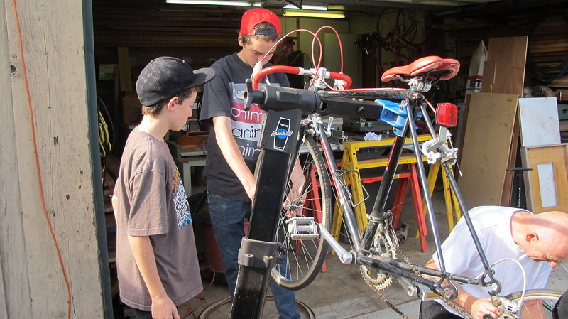 Jeffrey and David working on their bikes with Poppy. 2013
