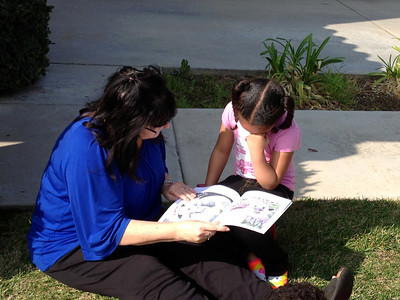 Grandma and Jaylie reading on the front lawn.