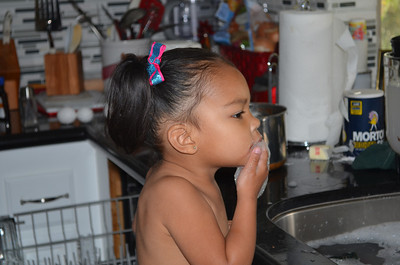 Kaylanni washing dishes or is she eating the bubbles.