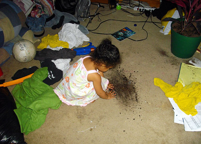 Jaylie spreading dirt on the bedroom floor.