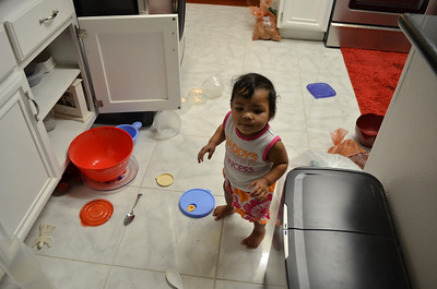 Kaylanni pulling out the bowls from the cabinets in the kitchen.