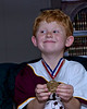 Josh(6) with soccer tournament medals.  Shot indoors with Betterbouncer on flash.