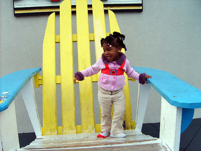 Kyra standing in big chair