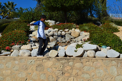 Noah walking on the 10 foot high wall in front of the water fountain and waterfall.