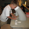 Hayden peering through a large microscope