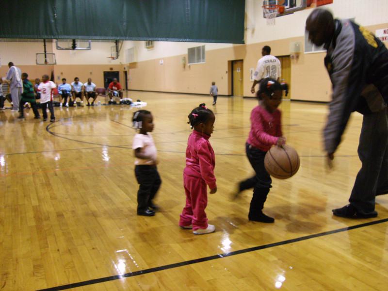 Lauryn & Vanessa watching Tenia dribble the basketball.