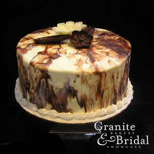 Marbleized Chocolate Swirl - Marble cake with custard filling. Iced in white buttercream and covered in swirled chocolate and white chocolate ganache. Topped with chocolate flowers.
