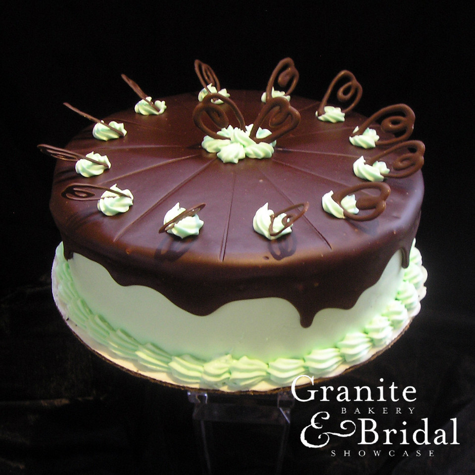 Chocolate Fudge Mint - Chocolate cake with custard & mint filling. Covered in mint buttercream and topped with a fudge drape and decorative chocolate pieces.