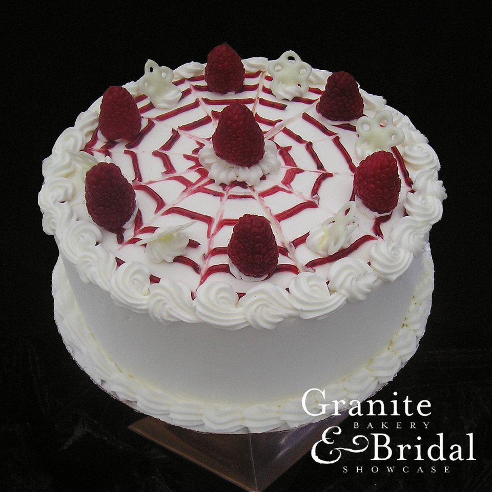 White Raspberry Stripe - White cake with raspberry filling. Covered in white buttercream with a raspberry swirl and topped with fresh raspberries and white chocolate pieces.