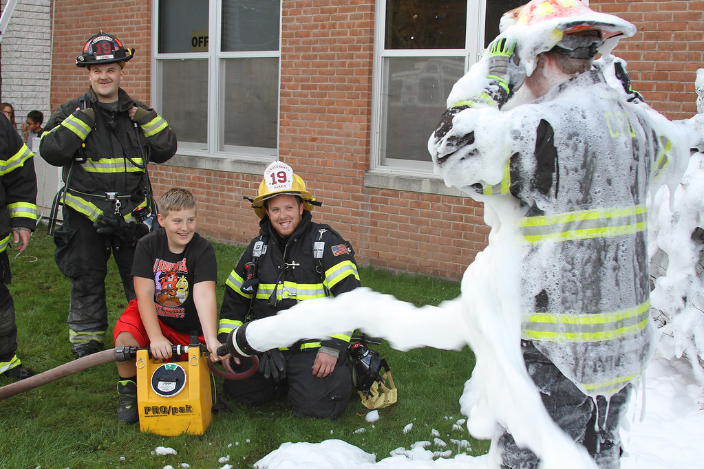 . Noah Wannamaker (second from left), a Grade 5 student at Grant D. Morse Elementary School, helps Zach Harris, a lieutenant with the Centerville/Cedar Grove Fire District, hold a foam machine while spraying firefighter Kyle Rompella, also of the Centerville/Cedar Grove Fire District, while firefighter Mike Laird (foreground) looks on.