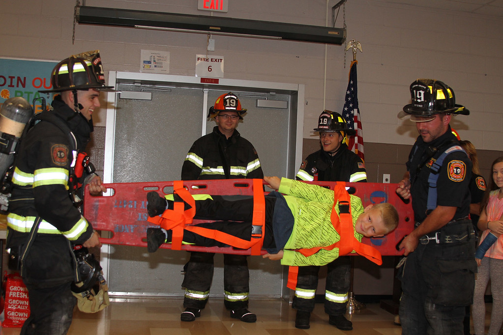 . Firefighters Michael Brako (left) and Michael Ivino (right) demonstrate a backboard securing and lifting technique with help from Grant D. Morse Elementary School Grade 5 student Dylan Benjamin.