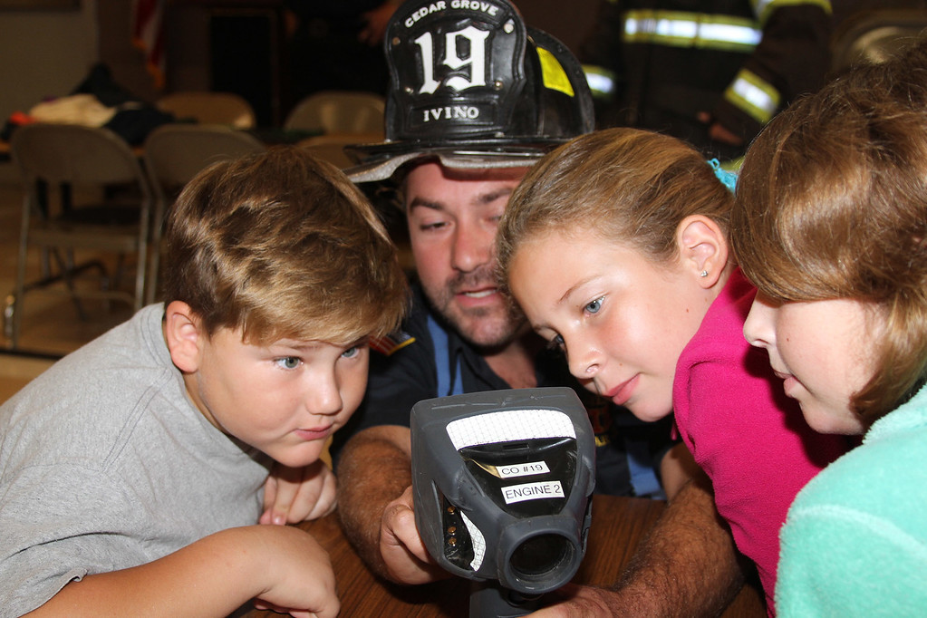 . Grant D. Morse Elementary School Grade 5 students Kenny Wamsley (left) and Caitlyn Rafferty (right) look at a thermal imaging camera displayed by firefighter Michael Ivino during a fire safety demonstration.