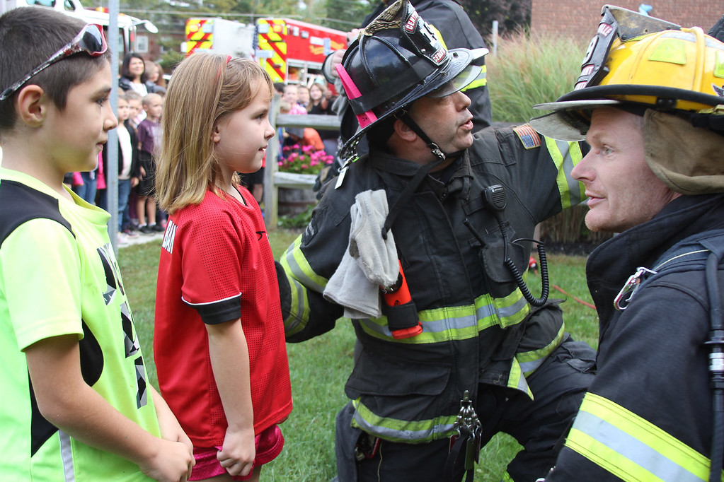 . Centerville/Cedar Grove Fire District firefighter Phil Butta (third from left) and Lieutenant Brian Ellsworth (right) explain what is happening during a window exit to Grant D. Morse Elementary School Grade 2 students Kalynn Taylor (second from left) and Kennedy Overbaugh.