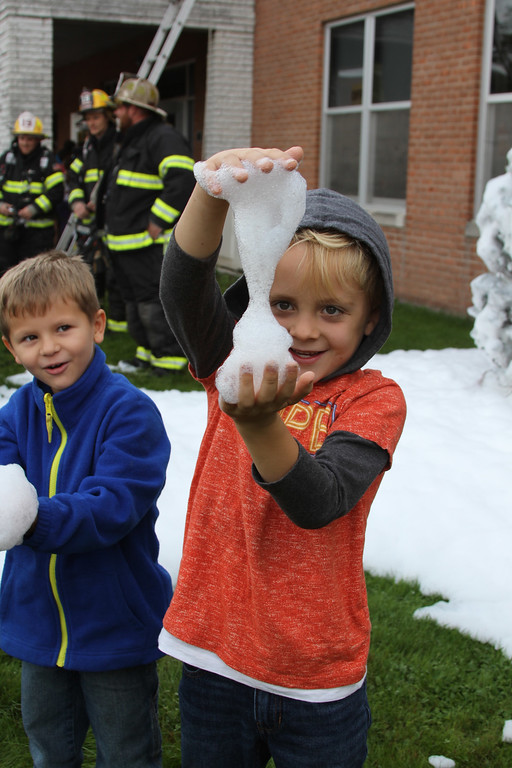 . Grant D. Morse Elementary School Grade 1 student Rhys Polston feels the foam used during a fire safety demonstration while Grade 1 student Andrew Finger (left) looks on.